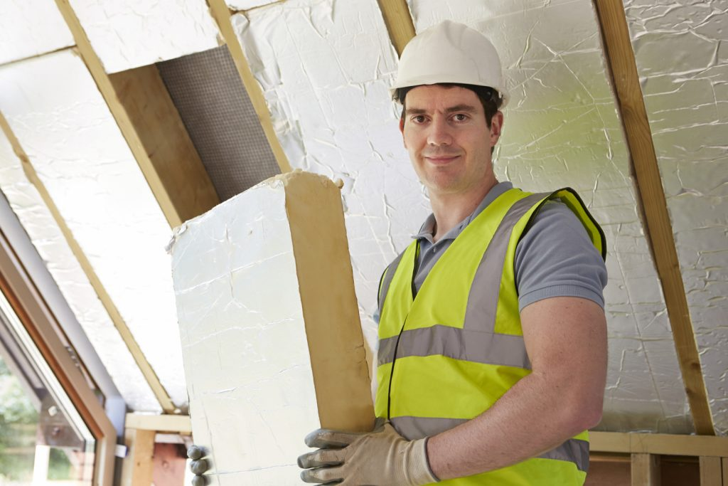 male worker smiling while holding insulation foam board